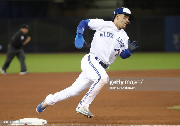 Devon Travis of the Toronto Blue Jays rounds third base and heads home to score a run in the fourth inning during MLB game action against the Atlanta...