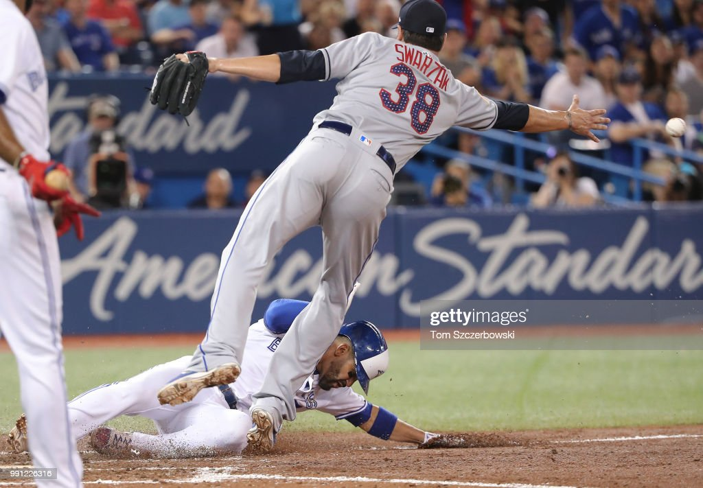 Devon Travis #29 of the Toronto Blue Jays slides across home plate to score a run on a wild pitch in the seventh inning during MLB game action as Anthony Swarzak #38 of the New York Mets reaches for the throw at Rogers Centre on July 3, 2018 in Toronto, Canada.
