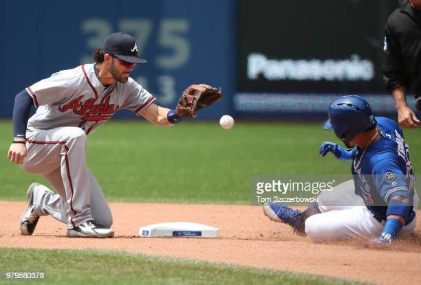 Devon Travis of the Toronto Blue Jays slides into second base with a double ahead of the throw to Dansby Swanson of the Atlanta Braves in the seventh...