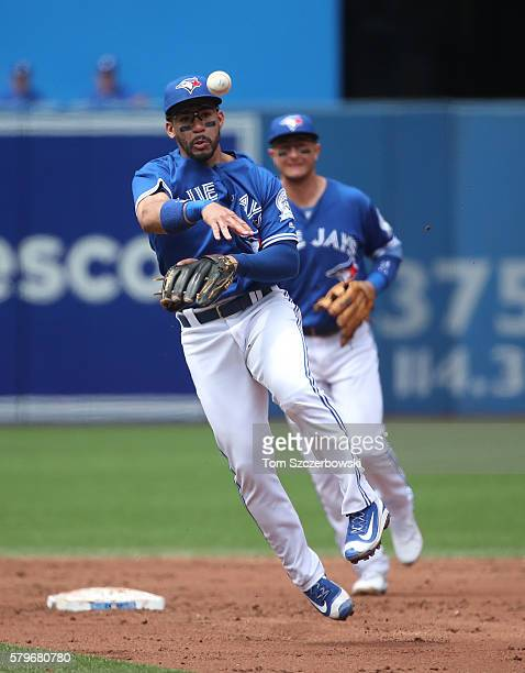 Devon Travis of the Toronto Blue Jays throws out the baserunner as Troy Tulowitzki watches in the third inning during MLB game action against the...