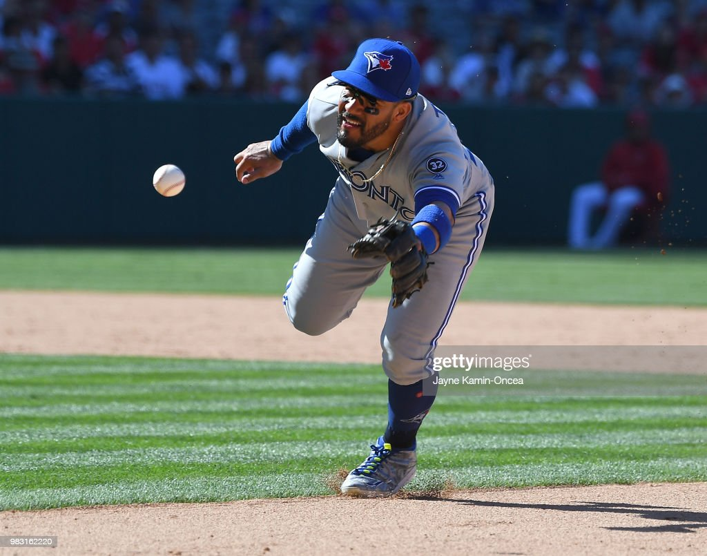 Devon Travis #29 of the Toronto Blue Jays tosses the ball to first but unable to get Justin Upton #8 of the Los Angeles Angels of Anaheim out in the tenth inning of the game at Angel Stadium on June 24, 2018 in Anaheim, California.