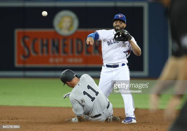 Devon Travis of the Toronto Blue Jays turns a double play in the fifth inning during MLB game action as Brett Gardner of the New York Yankees slides...