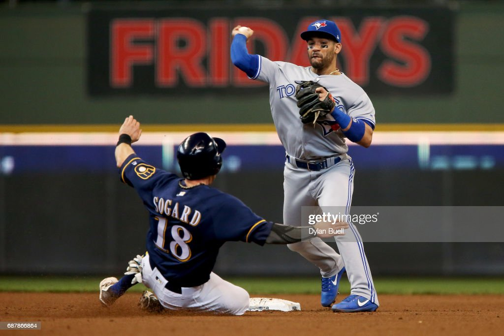 Devon Travis #29 of the Toronto Blue Jays turns a double play over Eric Sogard #18 of the Milwaukee Brewers in the fifth inning at Miller Park on May 24, 2017 in Milwaukee, Wisconsin.