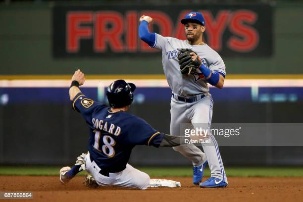Devon Travis of the Toronto Blue Jays turns a double play over Eric Sogard of the Milwaukee Brewers in the fifth inning at Miller Park on May 24 2017...