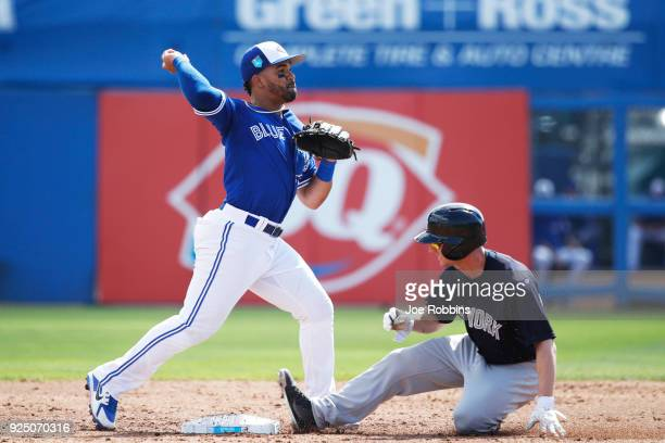Devon Travis of the Toronto Blue Jays turns a double play over Shane Robinson of the New York Yankees in the third inning of a Grapefruit League...
