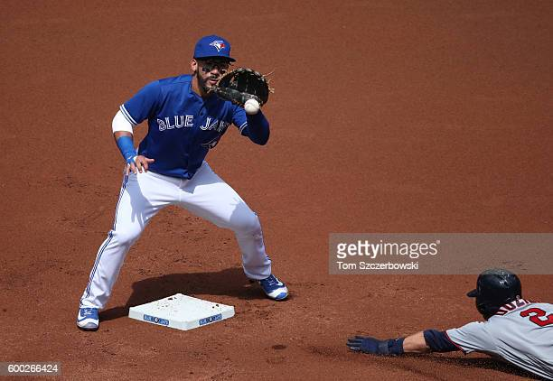 Devon Travis of the Toronto Blue Jays waits for the throw as Brian Dozier of the Minnesota Twins steals second base in the first inning during MLB...