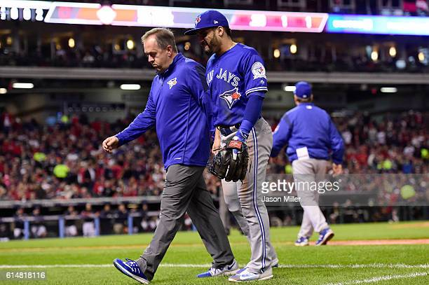 Devon Travis of the Toronto Blue Jays walks off the field after being injured in the fifth inning against the Cleveland Indians during game one of...