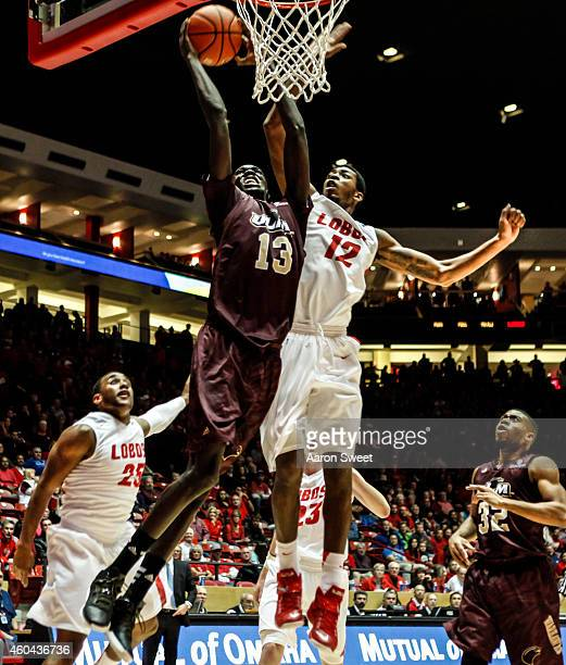 Devon Williams of the New Mexico Lobos attempts to block a shot by Majok Deng of the LouisianaMonroe Warhawks during their game at The WisePies Arena...