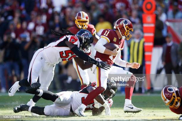 De'Vondre Campbell and Grady Jarrett of the Atlanta Falcons chase Alex Smith of the Washington Redskins in the second quarter of the game at...