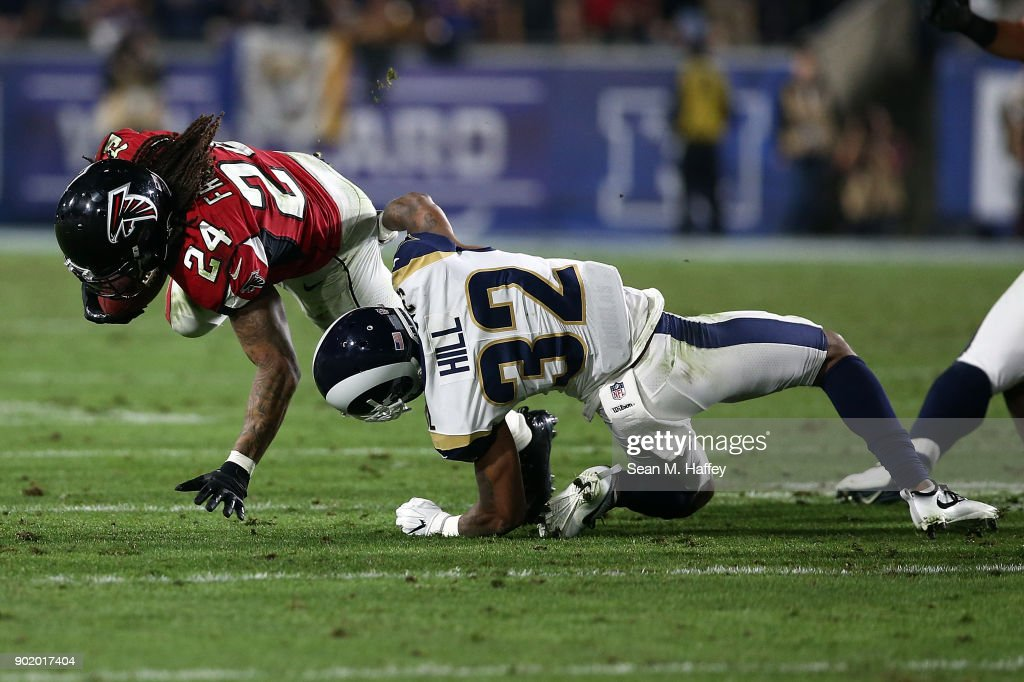Devonta Freeman #24 of the Atlanta Falcons breaks the tackle from Troy Hill #32 of the Los Angeles Rams during the NFC Wild Card Playoff Game at the Los Angeles Coliseum on January 6, 2018 in Los Angeles, California.