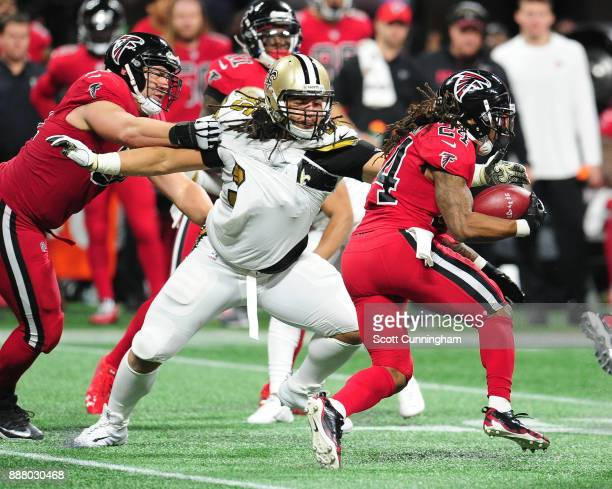 Devonta Freeman of the Atlanta Falcons carries the ball against Tyeler Davison of the New Orleans Saints at MercedesBenz Stadium on December 7 2017...