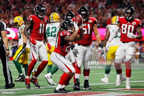 Devonta Freeman of the Atlanta Falcons celebrates after scoring a 1yard rushing touchdown during the first quarter against the Green Bay Packers at...