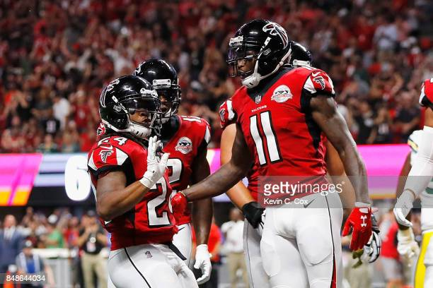 Devonta Freeman of the Atlanta Falcons celebrates with Julio Jones after scoring a 1yard rushing touchdown during the first quarter against the Green...
