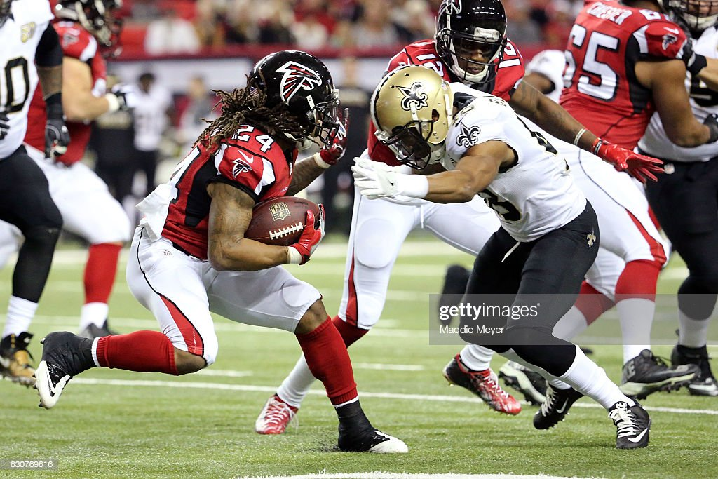 Devonta Freeman #24 of the Atlanta Falcons evades a tackle by Vonn Bell #48 of the New Orleans Saints during the first half at the Georgia Dome on January 1, 2017 in Atlanta, Georgia.