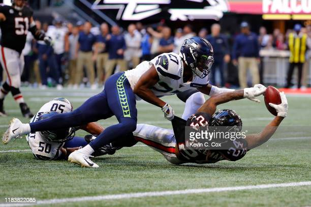 Devonta Freeman of the Atlanta Falcons fumbles the ball as he is tackled by Marquise Blair of the Seattle Seahawks in the second half at...