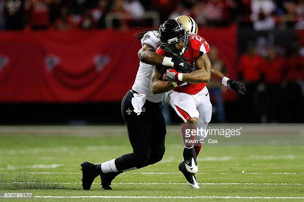 Devonta Freeman of the Atlanta Falcons is tackled by Dannell Ellerbe of the New Orleans Saints on a run during the first half at the Georgia Dome on...