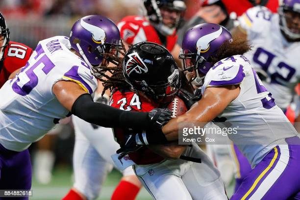 Devonta Freeman of the Atlanta Falcons is tackled by Eric Kendricks and Anthony Barr of the Minnesota Vikings during the first half at MercedesBenz...