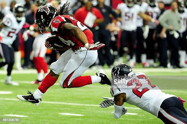 Devonta Freeman of the Atlanta Falcons runs past Quintin Demps of the Houston Texans in the first half at the Georgia Dome on October 4, 2015 in...