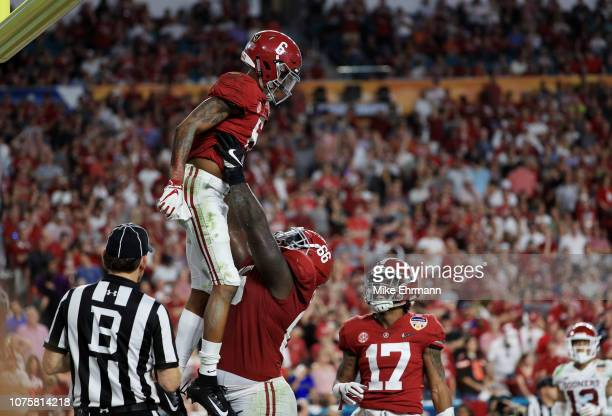 DeVonta Smith and Lester Cotton Sr #66 of the Alabama Crimson Tide celebrates after scoring a touchdown in the fourth quarter during the College...