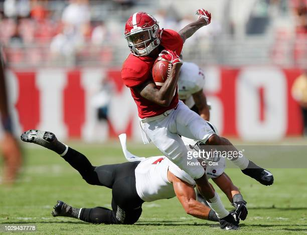 DeVonta Smith of the Alabama Crimson Tide breaks a tackle by BJ Edmonds of the Arkansas State Red Wolves at BryantDenny Stadium on September 8 2018...