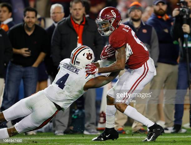 DeVonta Smith of the Alabama Crimson Tide breaks this tackle by Noah Igbinoghene of the Auburn Tigers on the way to a touchdown at BryantDenny...