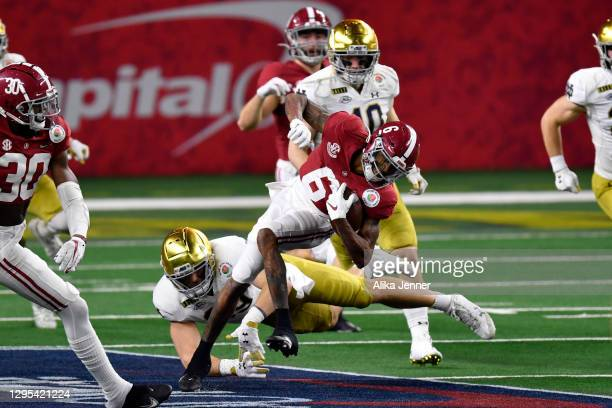 DeVonta Smith of the Alabama Crimson Tide eludes Brock Wright of the Notre Dame Fighting Irish during the College Football Playoff Semifinal at the...
