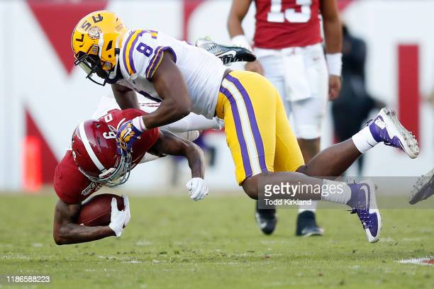 DeVonta Smith of the Alabama Crimson Tide is tackled by Patrick Queen of the LSU Tigers during the first half in the game at BryantDenny Stadium on...