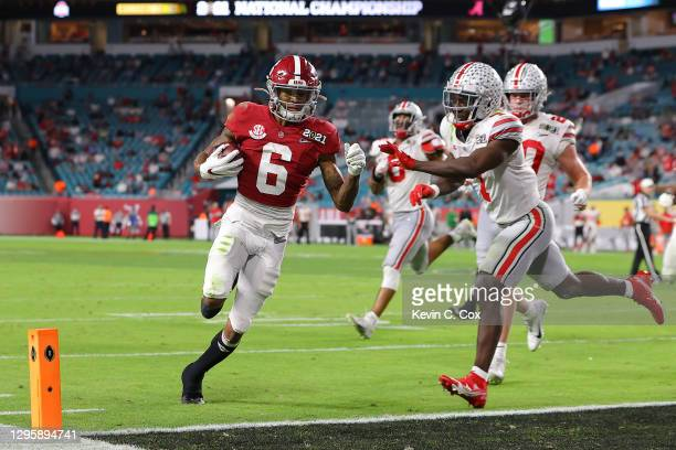 DeVonta Smith of the Alabama Crimson Tide rushes for a five yard touchdown ahead of Sevyn Banks of the Ohio State Buckeyes during the second quarter...