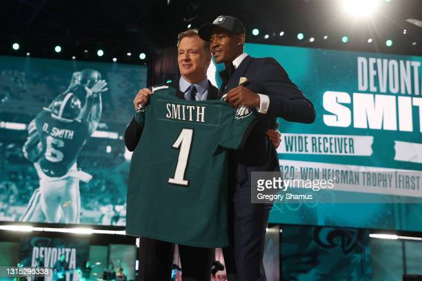 DeVonta Smith poses with NFL Commissioner Roger Goodell onstage after being selected 10th by the Philadelphia Eagles during round one of the 2021 NFL...