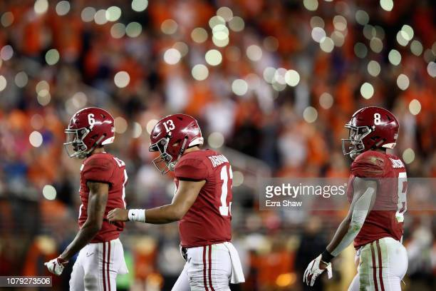 DeVonta Smith Tua Tagovailoa and Josh Jacobs of the Alabama Crimson Tide walk toward the sideline against the Clemson Tigers in the CFP National...