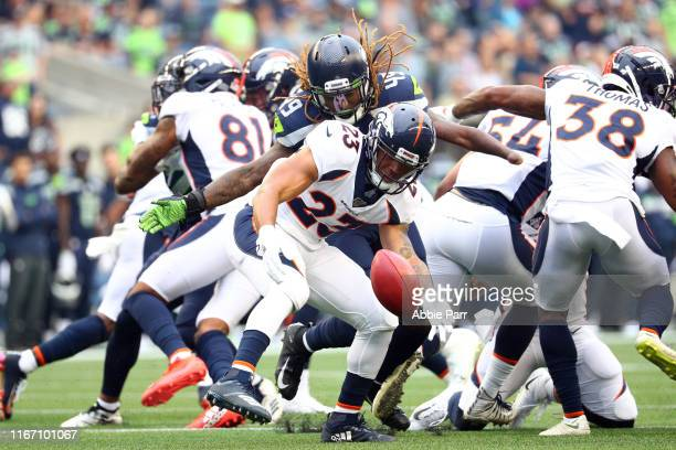 Devontae Booker of the Denver Broncos fumbles the ball against Shaquem Griffin of the Seattle Seahawks in the first quarter during their preseason...