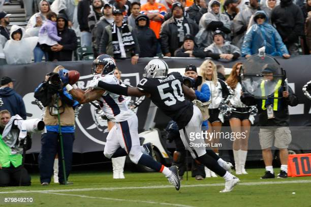 Devontae Booker of the Denver Broncos makes a catch as Bruce Irvin of the Oakland Raiders defends during the second quarter of their NFL football...