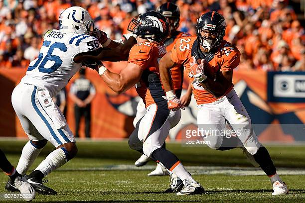 Devontae Booker of the Denver Broncos runs as Andy Janovich blocks Akeem Ayers of the Indianapolis Colts during the first quarter The Denver Broncos...