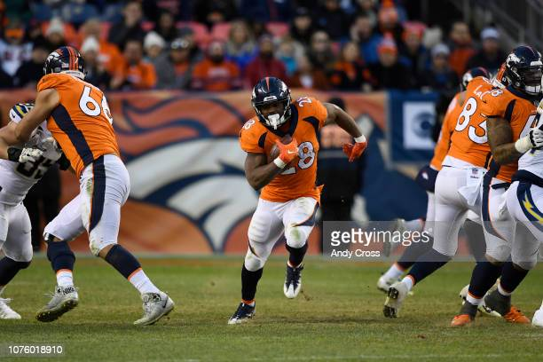 Devontae Booker of the Denver Broncos runs through a hole during the third quarter against the Los Angeles Chargers. The Denver Broncos hosted the...