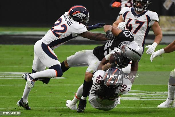 Devontae Booker of the Las Vegas Raiders is tackled by A.J. Johnson and Kareem Jackson of the Denver Broncos during the second quarter at Allegiant...