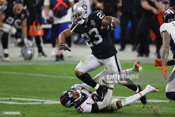 Devontae Booker of the Las Vegas Raiders runs against A.J. Bouye of the Denver Broncos during the second half at Allegiant Stadium on November 15,...
