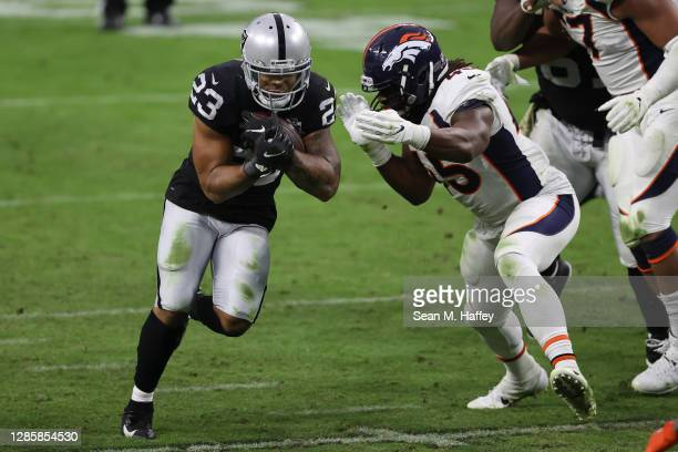 Devontae Booker of the Las Vegas Raiders runs against A.J. Johnson of the Denver Broncos during the second half at Allegiant Stadium on November 15,...