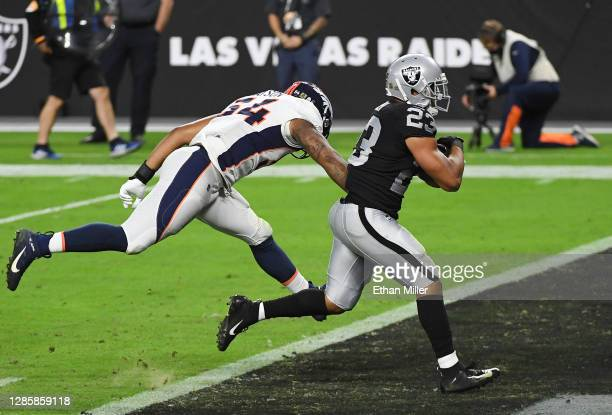Devontae Booker of the Las Vegas Raiders runs for a touchdown against Josh Watson of the Denver Broncos during the second half at Allegiant Stadium...