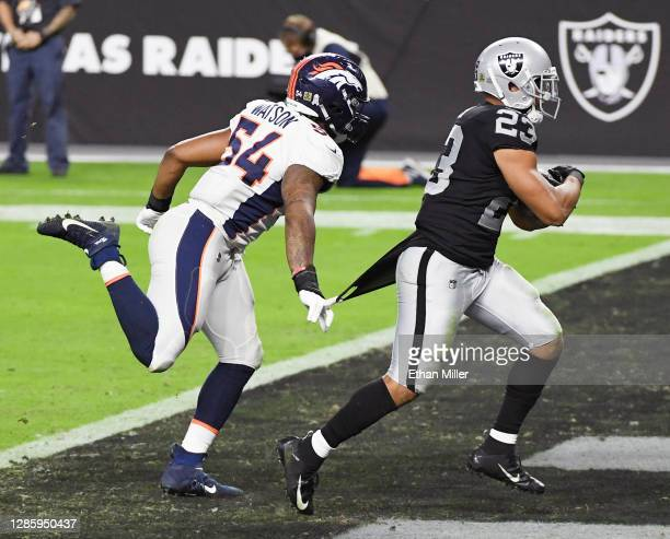 Devontae Booker of the Las Vegas Raiders runs for a touchdown against Josh Watson of the Denver Broncos during the second half of their game at...
