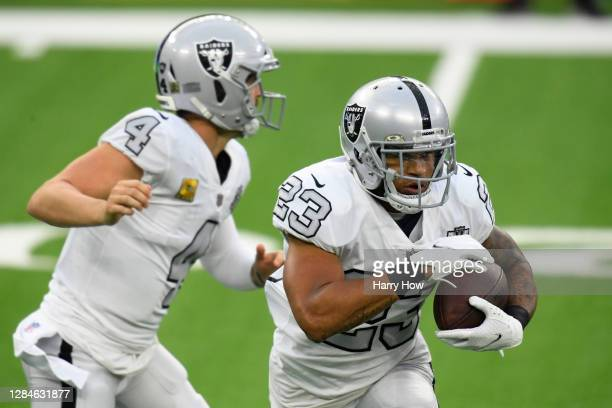 Devontae Booker of the Las Vegas Raiders takes a handoff from Derek Carr in the third quarter while playing the Los Angeles Chargers at SoFi Stadium...