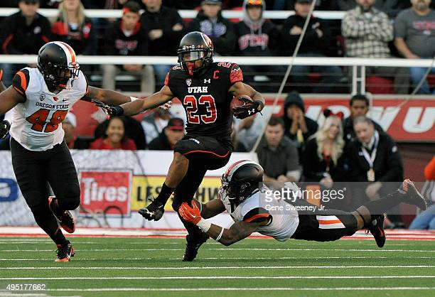 Devontae Booker of the Utah Utes runs for yardage in the first quarter between Jaswha James and Justin Strong of the Oregon State Beavers at...
