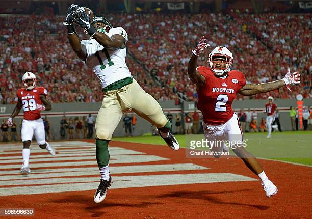 DeVonte Dedmon of the William Mary Tribe makes a touchdown catch against Mike Stevens of the North Carolina State Wolfpack during their game at...