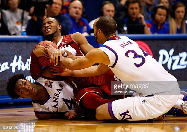 Devonte' Graham and Perry Ellis of the Kansas Jayhawks wrestle Dante Buford of the Oklahoma Sooners for a loose ball during the game at Allen...