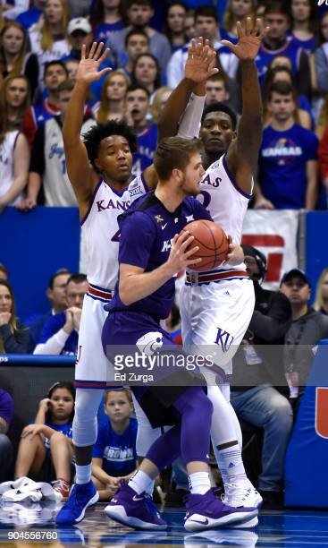 Devonte' Graham and Silvio De Sousa of the Kansas Jayhawks defend Dean Wade of the Kansas State Wildcats in the first half at Allen Fieldhouse on...