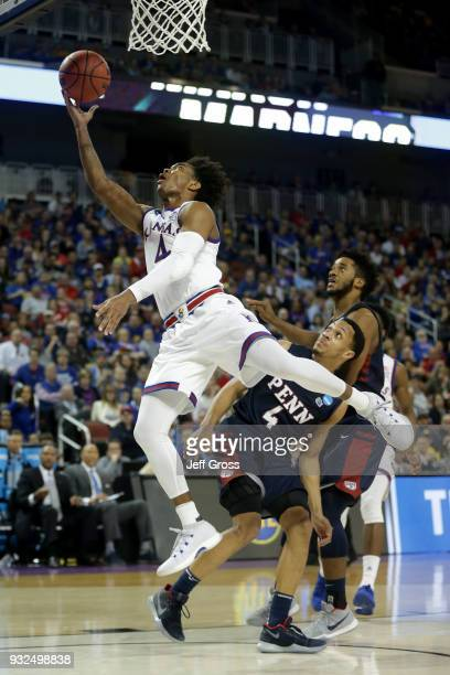Devonte' Graham of the Kansas Jayhawks attempts a shot past Darnell Foreman of the Pennsylvania Quakers in the second half during the first round of...