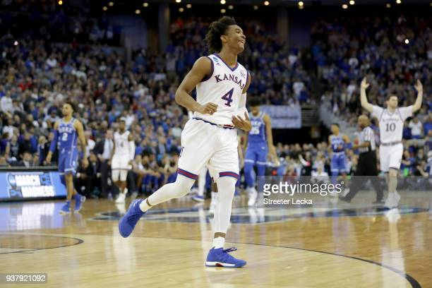 Devonte' Graham of the Kansas Jayhawks celebrates a play against the Duke Blue Devils during overtime in the 2018 NCAA Men's Basketball Tournament...