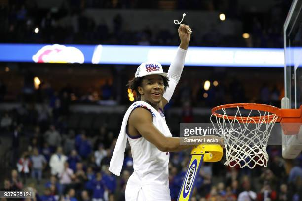 Devonte' Graham of the Kansas Jayhawks celebrates cutting down the net after defeating the Duke Blue Devils with a score of 81 to 85 in the 2018 NCAA...