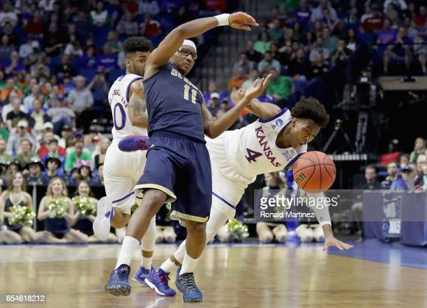 Devonte' Graham of the Kansas Jayhawks collides with Chima Moneke of the UC Davis Aggies during the first round of the 2017 NCAA Men's Basketball...