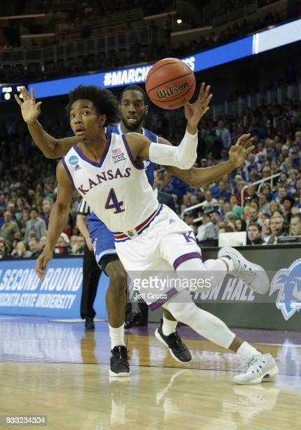 Devonte' Graham of the Kansas Jayhawks drives against Ismael Sanogo of the Seton Hall Pirates in the first half during the second round of the 2018...