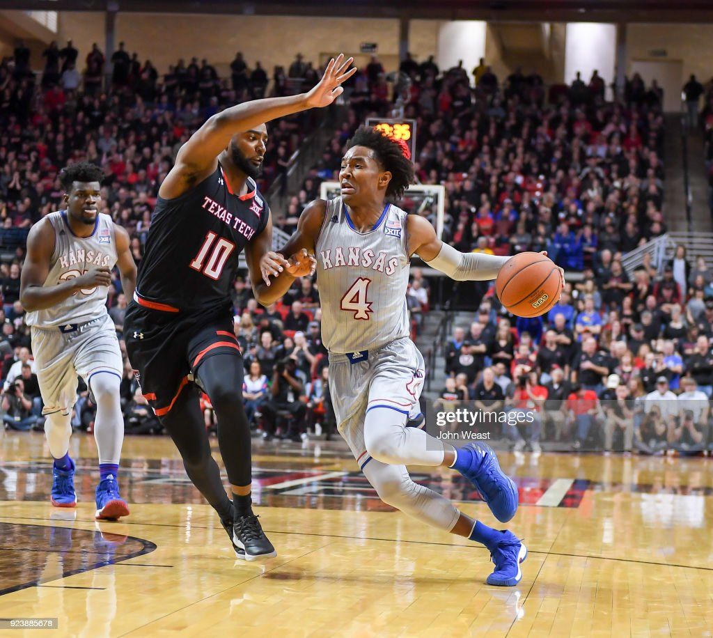 Devonte' Graham #4 of the Kansas Jayhawks drives around Niem Stevenson #10 of the Texas Tech Red Raiders during the second half of the game on February 24, 2018 at United Supermarket Arena in Lubbock, Texas. Kansas defeated Texas Tech 74-72.